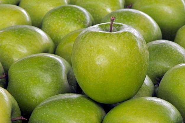 Grüne apfelnahaufnahme über stapel von äpfeln