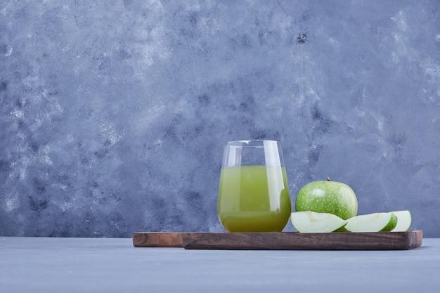 Grüne apfelscheiben mit einem glas saft.