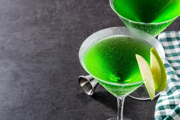 Grüne appletini-cocktails im glas auf schwarzer oberfläche