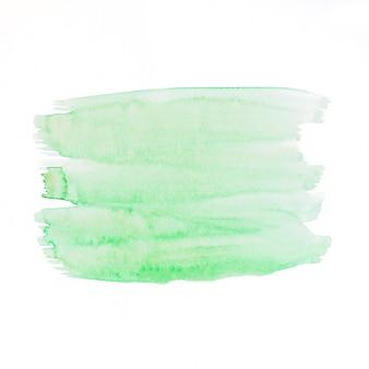 Grüne aquarellbürste schürt auf weißem hintergrund