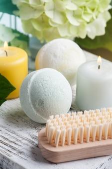 Grüne aromabadebomben im spa-stillleben auf weißem holz mit hortensienblumen und -blättern