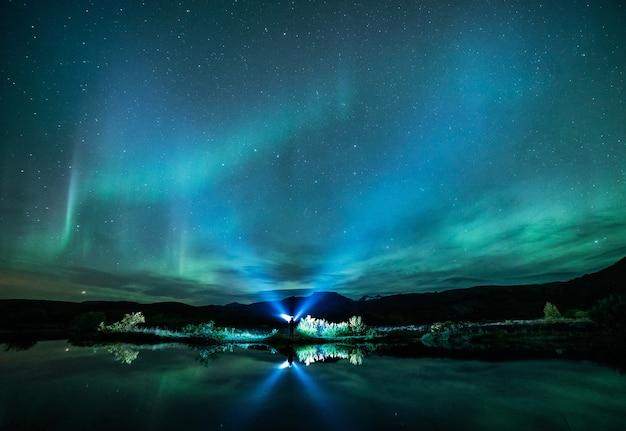 Grüne aurora leuchtet über dem gewässer