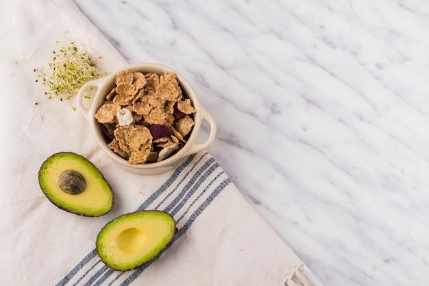 Grüne avocado mit getreide in der schüssel auf tabelle