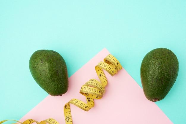 Grüne avocadofrucht und ein verdrehtes gelbes maßband auf einem grünen rosa