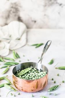 Grüne babyerbsen in der pfanne auf weiß