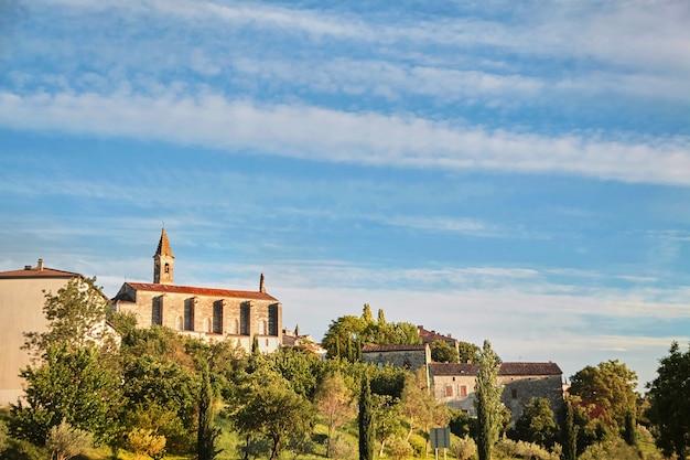 Grüne bäume und gebäude und kirche mit einem glockenturm in barjac - südfrankreich