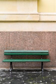 Grüne bank auf der straße vor der wand. russland, sankt petersburg