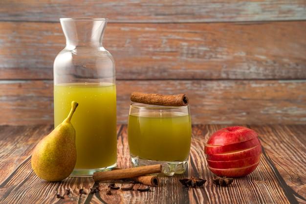 Grüne birne und roter apfel mit einem glas saft