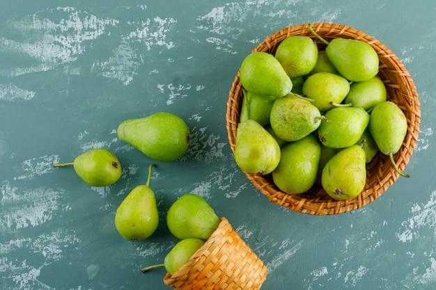 Grüne birnen in flachen körben lagen auf einem gips-tisch