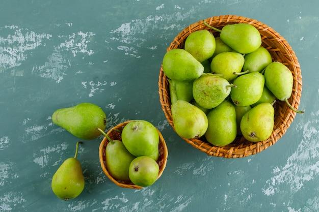 Grüne birnen in körben auf einem gips-tisch. flach liegen.