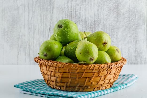 Grüne birnen mit küchentuch in einem korb auf weiß und grungy.