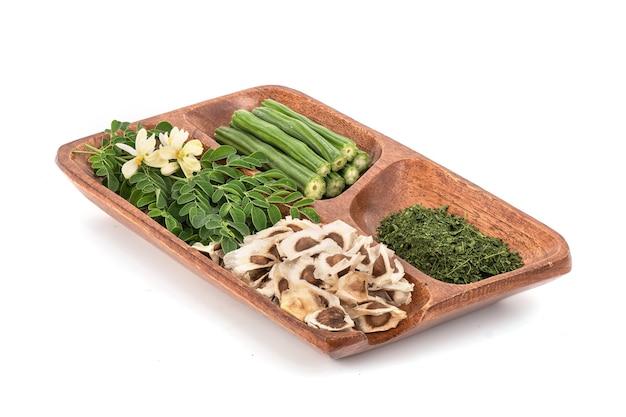 Grüne blätter, blumen, pulver, samen und früchte von moringa lokalisiert auf weißem hintergrund.