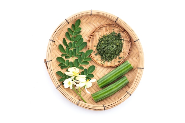 Grüne blätter, blumen, pulver und früchte von moringa lokalisiert auf weißem hintergrund. draufsicht, flache lage.