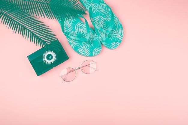 Grüne blätter; kamera; sonnenbrille und paar flip flops vor rosa hintergrund