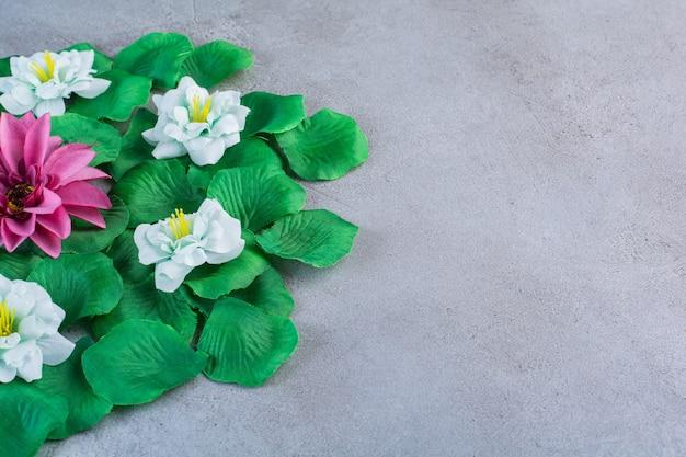 Grüne blätter mit lila und weißen blüten auf grau