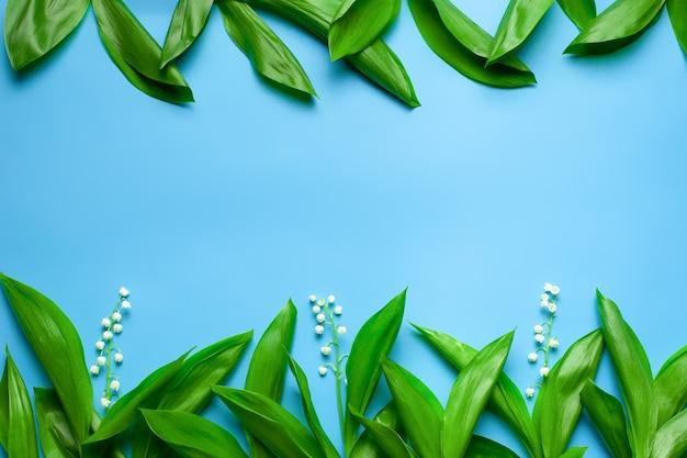 Grüne blätter und kleine blumensträuße von maiglöckchen als blumengrenze mit kopienraum flach liegen ...