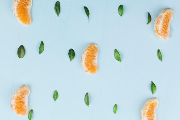 Grüne blätter und mandarinenstücke