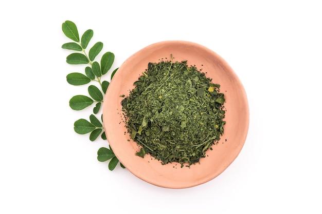 Grüne blätter und pulver von moringa lokalisiert auf weißem hintergrund. draufsicht, flache lage.