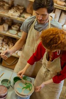 Grüne blumen. fokussiertes junges paar, das sich auf kunstwerke konzentriert, während es den ganzen tag in der töpferwerkstatt bleibt?