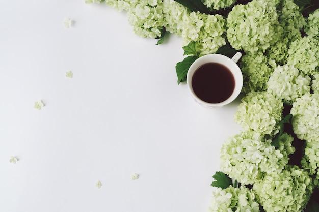 Grüne blumen und gelbe schale mit tee auf einem weißen hintergrund