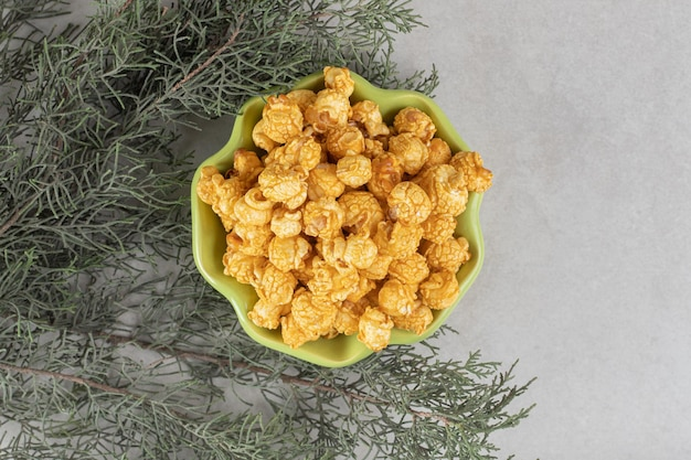 Grüne blumenförmige schale voll karamellpopcorn, verschachtelt zwischen ästen auf marmortisch.