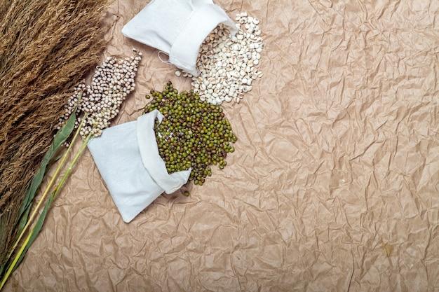 Grüne bohne, hirse, auf braunem papierhintergrund