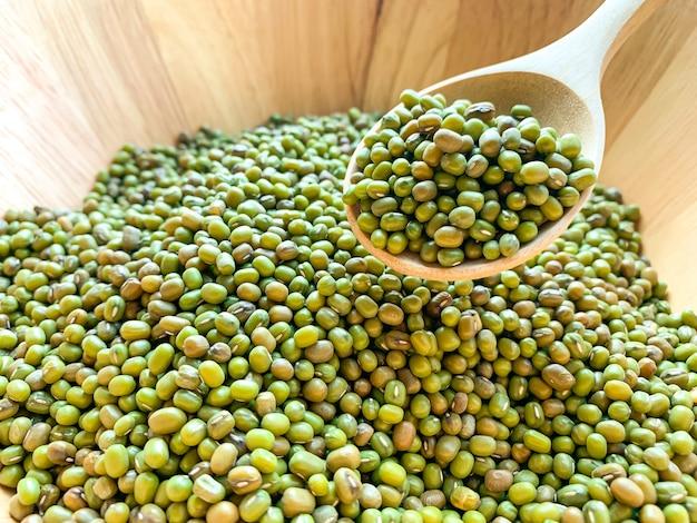 Grüne bohnen auf einem holzlöffel in einer holzschale