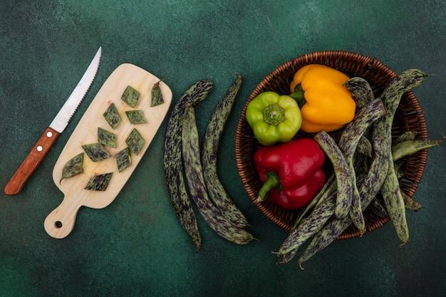 Grüne bohnen der draufsicht mit paprika in einem korb mit einem schneidebrett mit einem messer auf einem grünen hintergrund