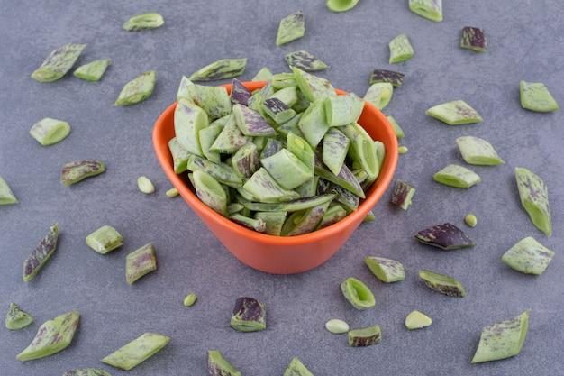 Grüne bohnen in einem behälter oder einer platte auf betonhintergrund.