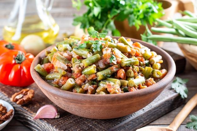 Grüne bohnen mit gemüse und tomaten. essen kochen hintergrund, vintage rustikalen holztisch.