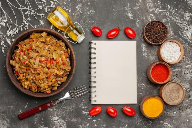 Grüne bohnen mit tomaten die appetitlichen grünen bohnen und tomaten neben der gabel flasche öl schüsseln mit bunten gewürzen tomaten und weißes notizbuch auf dem tisch