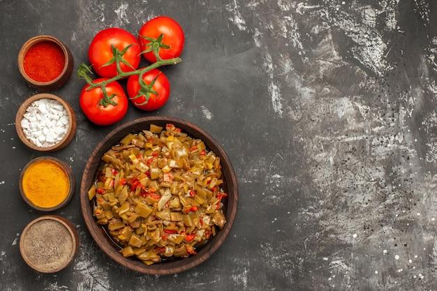 Grüne bohnen und gewürze grüne bohnen in der schüssel neben vier schüsseln mit gewürzen und tomaten mit stielen auf dem dunklen tisch