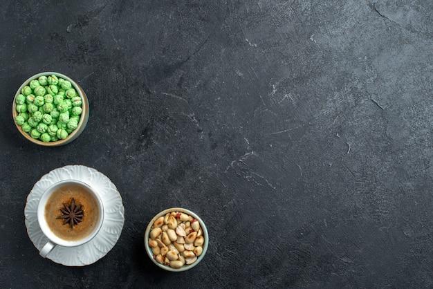 Grüne bonbons der draufsicht mit tasse kaffee und nüssen auf süßem keks des grauen hintergrundkekszuckerkuchens