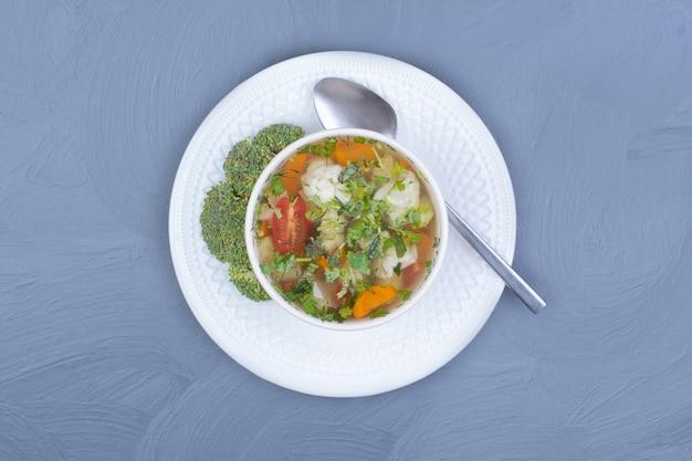 Grüne brokkolisuppe in brühe mit gemüse