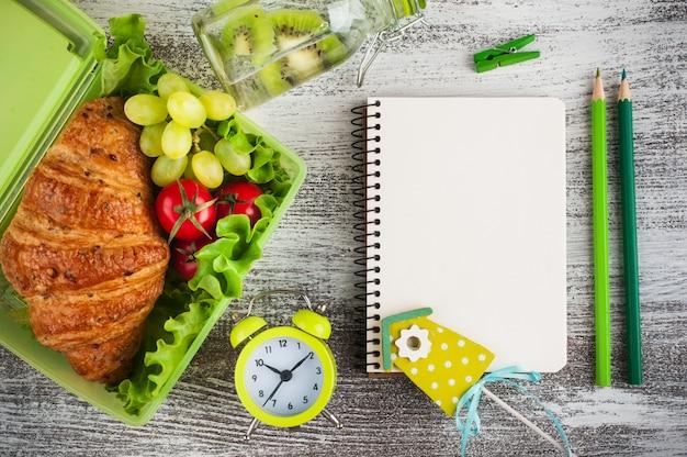 Grüne brotdose mit snack und einem notizbuch