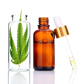 Grüne cannabisblätter mit flaschen mit ätherischen ölen und tropfenölreflexion lokalisiert auf weiß