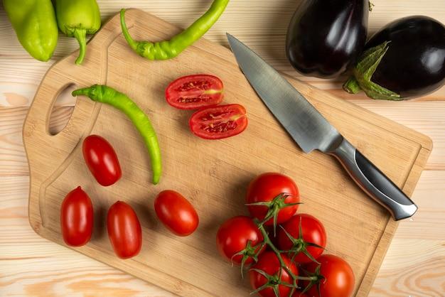 Grüne chilis und geschnittene tomaten auf dem holztisch