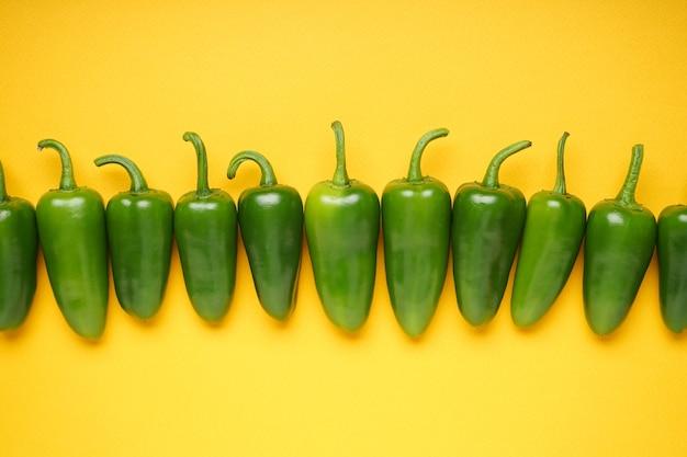 Grüne chilischote. jalapenopfeffer auf gelbem hintergrund, ansicht von oben.
