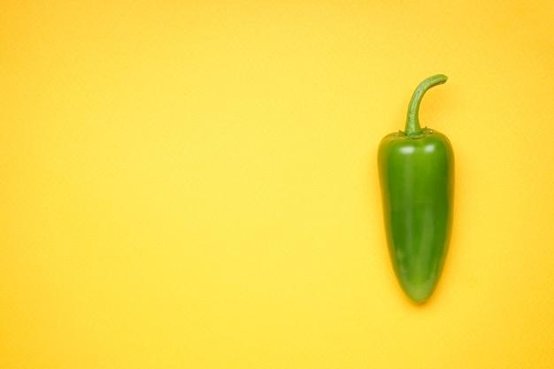 Grüne chilischote. jalapenopfeffer auf gelbem hintergrund, platz für text. ansicht von oben.