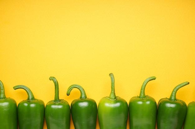 Grüne chilischote. jalapenopfeffer auf gelbem hintergrund, platz für text, ansicht von oben.