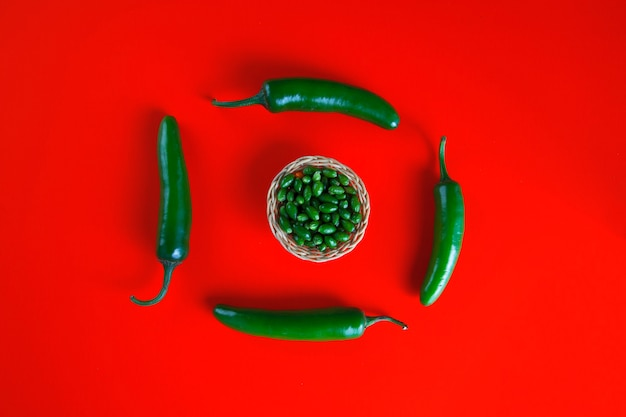 Grüne chilischoten lokalisiert auf roter wand