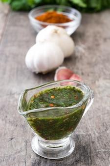 Grüne chimichurri-soße und -bestandteile auf holztisch
