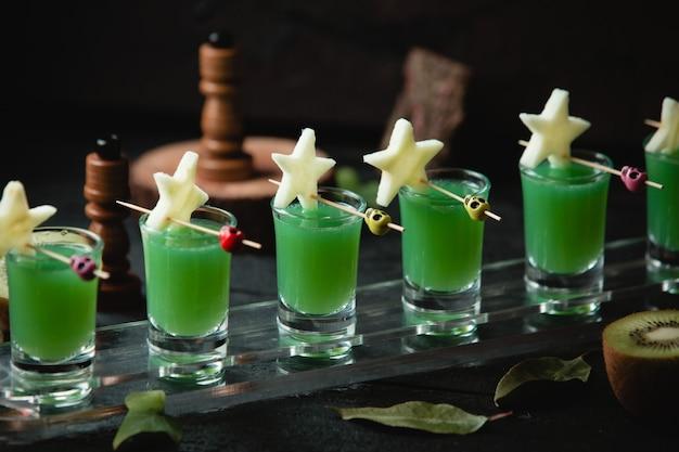 Grüne cocktails in kleinen gläsern mit sternförmigen ansteckern.