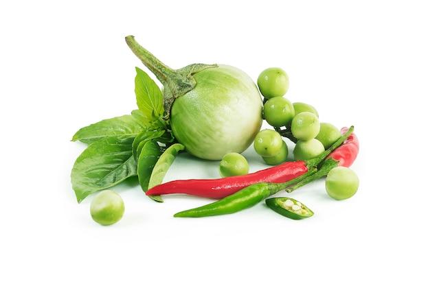 Grüne curry-zutaten des thailändischen nahrungshühners isoliert. geviertelte auberginen, erbsen-auberginen, grüner und roter chili-pfeffer, basilikumblätter und kokosmilch.