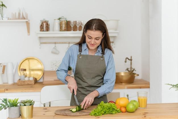 Grüne diät, eine frau schneidet gurken. schöne frau, die zu hause leckeren gemüsesalat in der küche zubereitet.