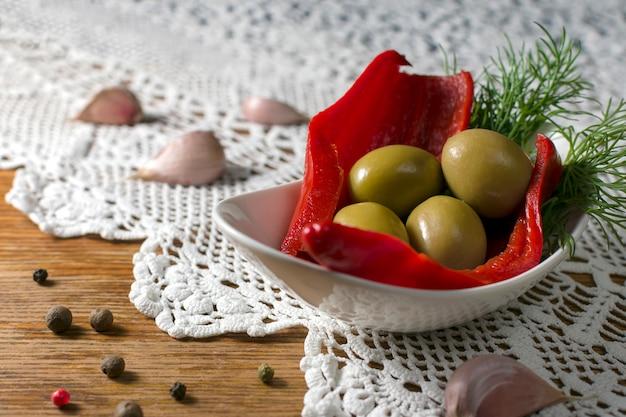 Grüne eingelegte oliven serviert auf einem teller mit rotem pfeffer und dill. komposition auf altmodischem tisch mit handgefertigter tischdecke. hausgemachtes fermentiertes gemüse