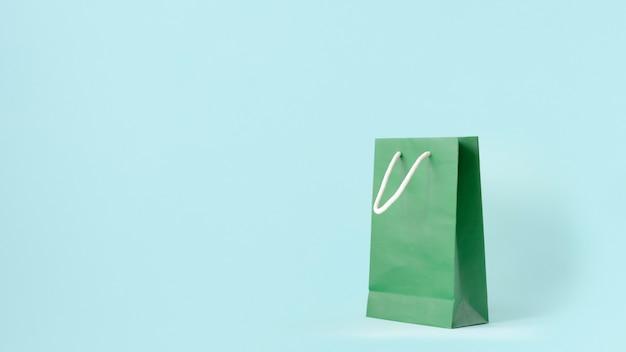 Grüne einkaufstasche auf tadellosem pastellfarbhintergrund.