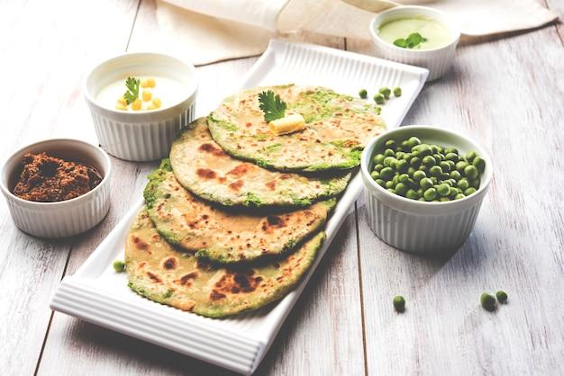 Grüne erbsen gefülltes fladenbrot oder matar ka paratha ist ein traditionelles essen aus nordindien. serviert mit mangogurke, über stimmungsvollem hintergrund, selektiver fokus