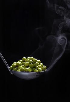 Grüne erbsen in einer dampfenden kelle auf einem dunklen hintergrund