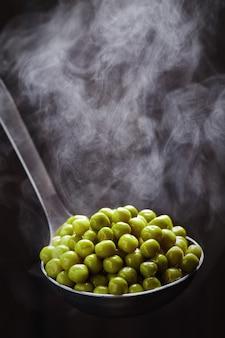 Grüne erbsen in einer pfanne mit dampf